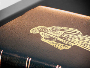 A black leather bible with a Santa Muerte logo engraved on it.