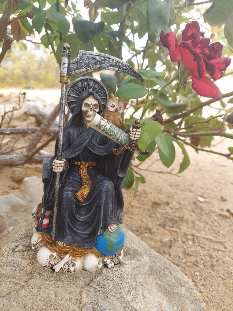 Seated Santa Muerte statue holding a dollar bill.